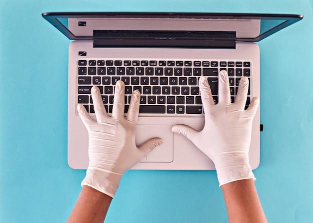 Ręce człowieka z lateksowymi rękawiczkami, wpisując na klawiaturze laptopa