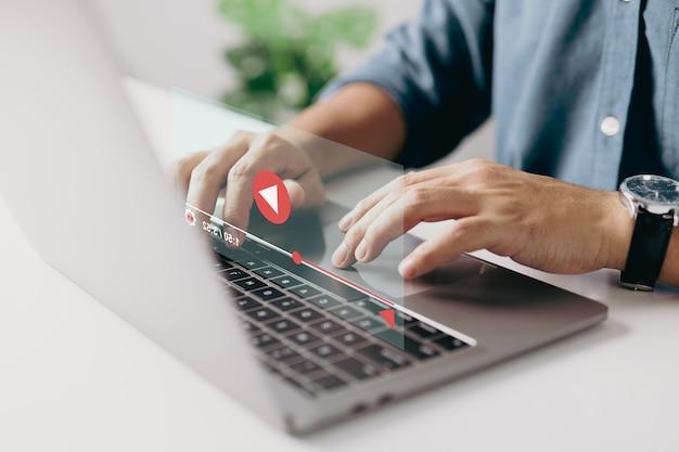 Ręce człowieka za pomocą laptopa do przesyłania strumieniowego online oglądania wideo w programie internetowym lub samouczku