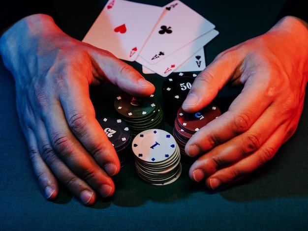 Ręce człowieka zabierają żetony do pokera