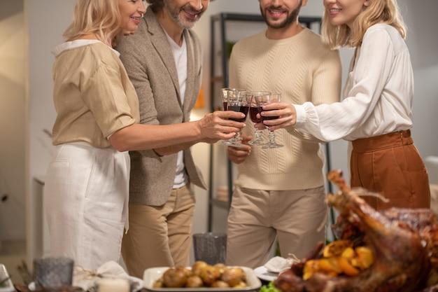 Ręce czterech uśmiechniętych członków rodziny w codziennej odzieży brzęczące z kieliszkami czerwonego wina nad świątecznym stołem podawane na obchody święta dziękczynienia