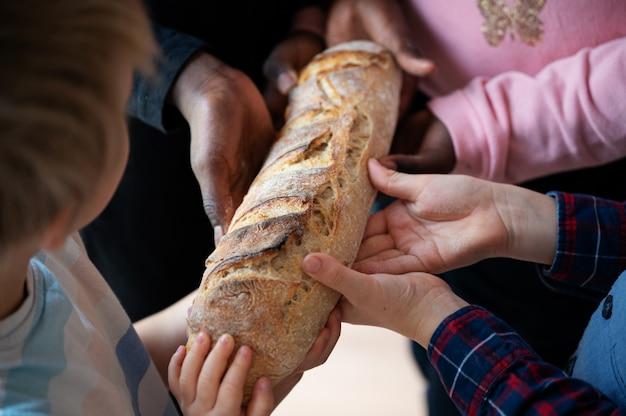Ręce czworga dzieci, czarno-białe, trzymające jeden bochenek chleba