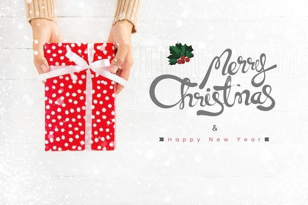 Ręce dając czerwone pudełko z wesołych świąt i szczęśliwego nowego roku tekst