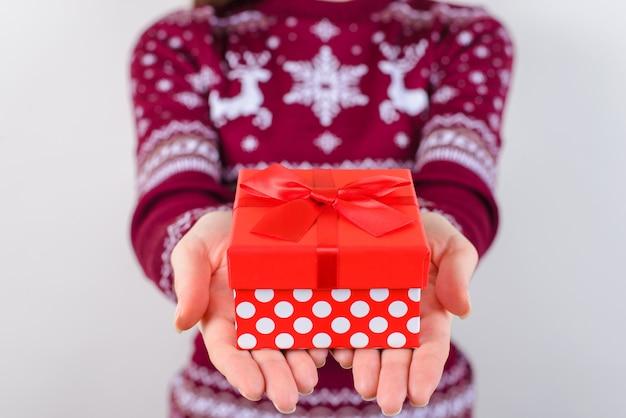 Ręce dające mały czerwony prezent