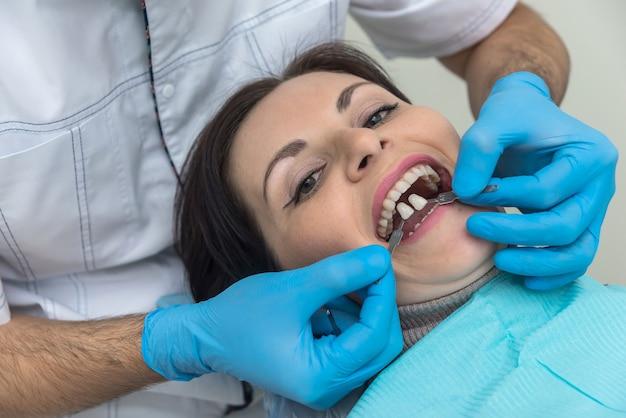 Ręce dentysty z próbnikiem zębów i pacjentem