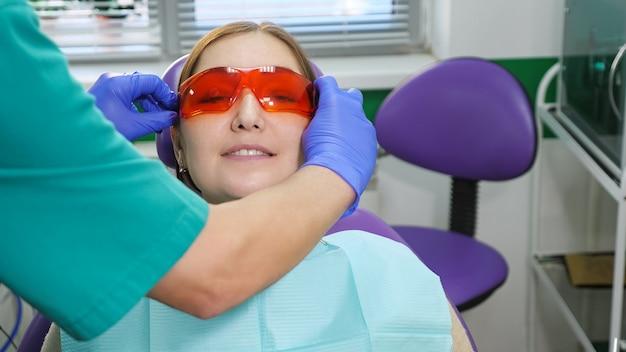 Ręce dentysty zakładają okulary na pacjentkę, młodą kobietę siedzącą na fotelu dentystycznym przed badaniem.