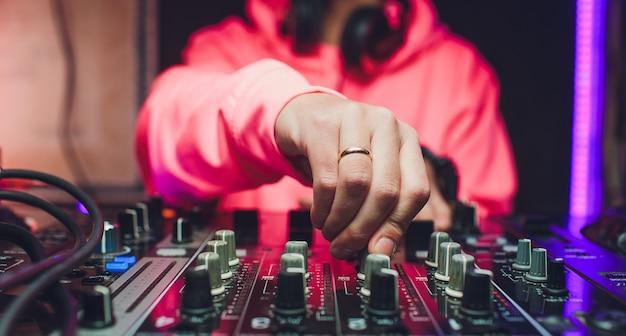 Ręce dj-a miksują utwory na cyfrowym gramofonie i oprogramowanie na laptopie z profesjonalnym oprogramowaniem do miksowania.