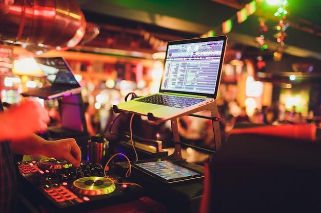 Ręce dj miksują ścieżki na cyfrowym gramofonie i oprogramowanie na laptopie z profesjonalnym oprogramowaniem do miksowania
