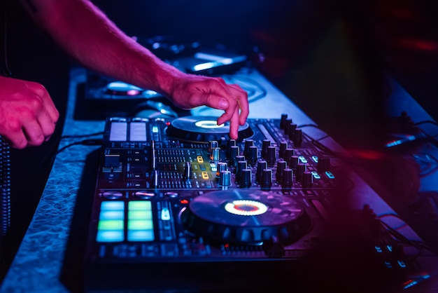 Ręce dj miksujące muzykę na profesjonalnym kontrolerze w kabinie