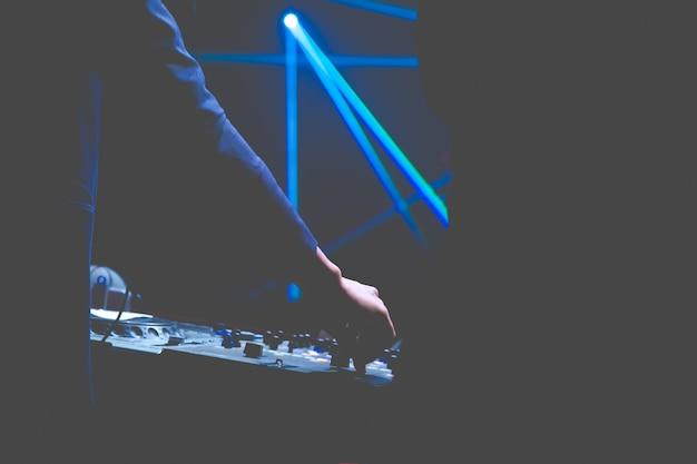 Ręce dj zmieniają różne elementy sterujące na pokładzie dj