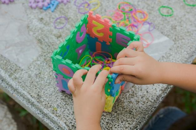 Ręce dla dzieci trzymają puzzle abc
