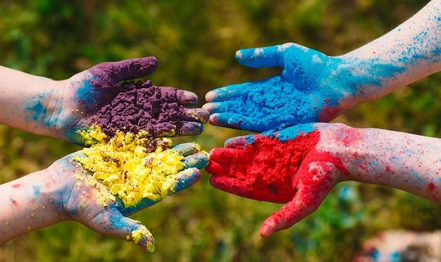 Ręce / dłonie młodych ludzi pokryte fioletowymi, żółtymi, czerwonymi, niebieskimi kolorami festiwalu holi na białym tle
