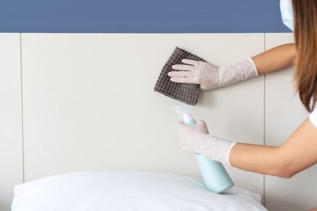 Ręce do czyszczenia powierzchni w sypialni w domu. zbliżenie.