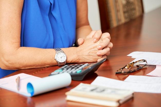 Ręce dojrzałej kobiety siedzącej przy stole z rachunkami za media, wypłatami i kalkulatorem
