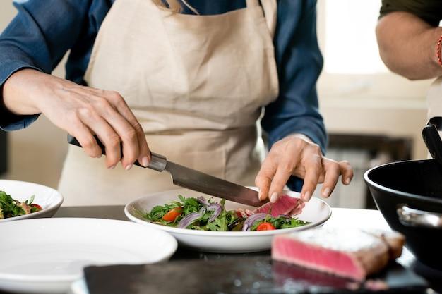 Ręce dojrzałej samicy kładą kawałek wędzonego mięsa na talerzu z gotowaną na parze fasolką szparagową z rukolą, posiekaną cebulą i pomidorkami koktajlowymi