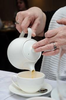 Ręce dorosłej (starszej) kobiety (babci) wlewają herbatę z białego czajnika do białego klasycznego kubka