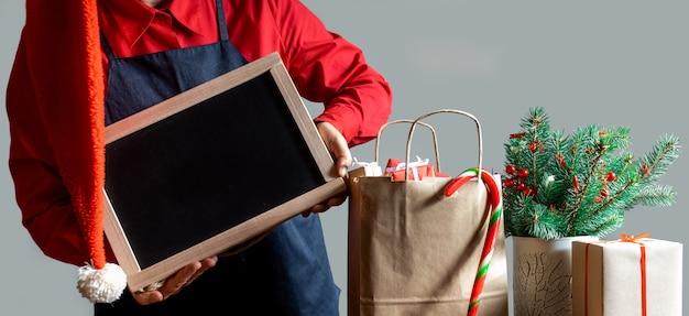 Ręce dostawcy trzymają tablicę na zakupy w pobliżu torby do pakowania, pudełek na prezenty i choinki.