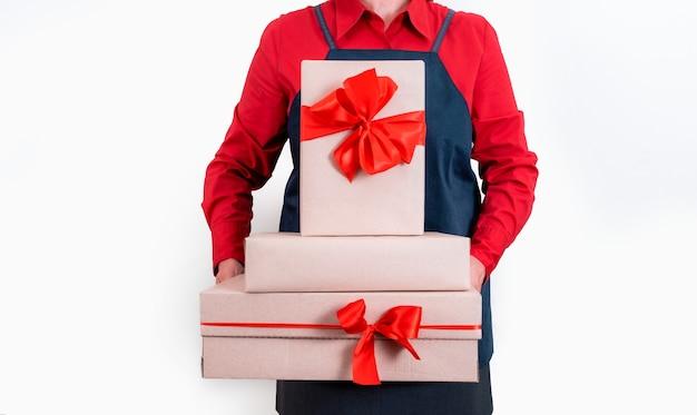 Ręce dostawcy w czerwonej koszuli trzymają pudła i prezenty