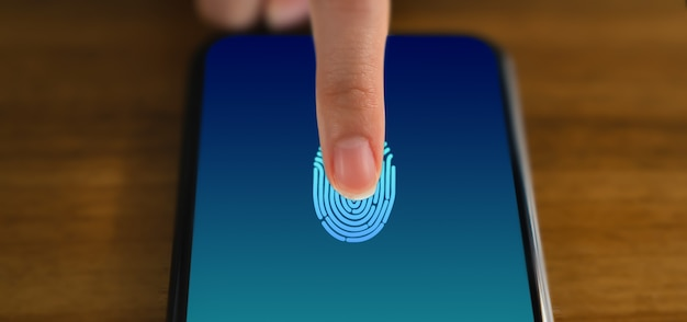 Ręce dotykają smartfona i wyświetlają ekran skanera linii papilarnych, aby uzyskać dostęp online.