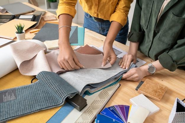 Ręce dwóch projektantek wnętrz stoją przy biurku i podczas pracy w studio wybierają próbki tkanin do jednego z nowych zamówień