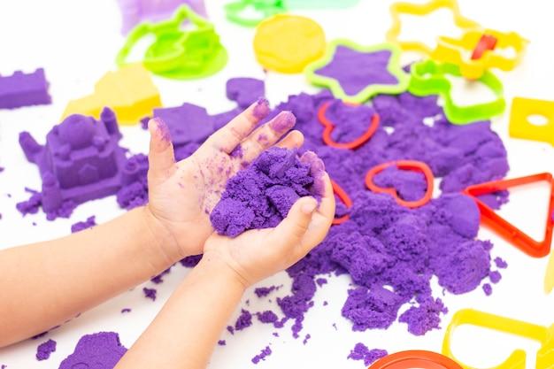 Ręce dzieci bawią się kinetycznym piaskiem w kwarantannie. fioletowy piasek na białym stole. koronawirus pandemia
