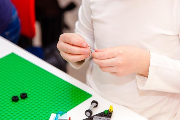 Ręce dzieci bawią się kolorowymi klockami lego na białym stole
