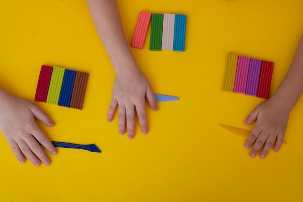 Ręce dzieci bawiących się kolorową plasteliną