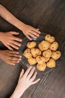 Ręce dzieci biorących własnoręcznie upieczone ciasteczka na stole, gdy oboje stoją przy stole w kuchni