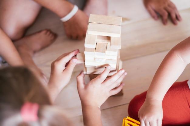 Ręce dzieci grają w grę z wieżą wykonaną z drewnianych klocków