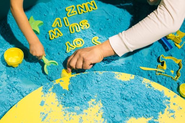 Ręce dzieci i dorosłych bawiące się niebieskim piaskiem kinetycznym. terapia sztuką. łagodzenie stresu i napięcia. wrażenia dotykowe. rozwój umiejętności motorycznych. koncentracja i uwaga.