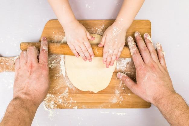Ręce dzieci i taty toczyły ciasto