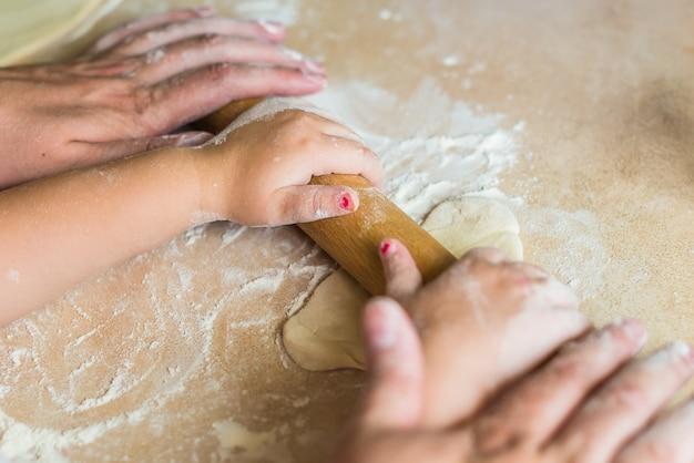 Ręce dzieci i taty toczyły ciasto.