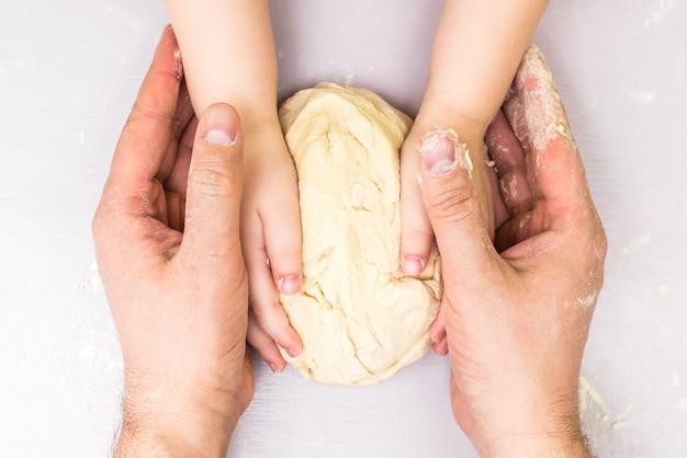 Ręce dzieci i taty tworzą ciasto