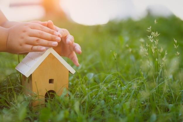 Ręce dzieci obejmujące model domu z drewna. koncepcja ubezpieczenia domu