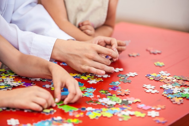 Ręce dzieci, przyjaciół układają puzzle na kolorowym stole. połączenie, zagadka, przyjaźń, unia.