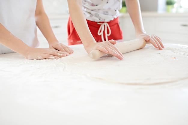 Ręce dzieci rozwałkują ciasto do pizzy na białym stole. wspólna zabawa w kuchni. widok z góry.