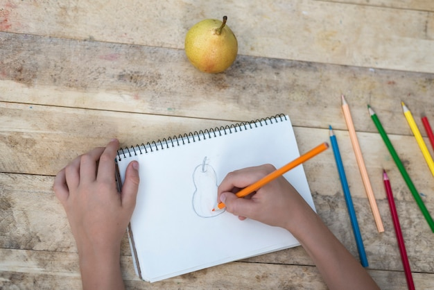 Ręce dzieci rysują gruszkę za pomocą kolorowych ołówków. widok z góry