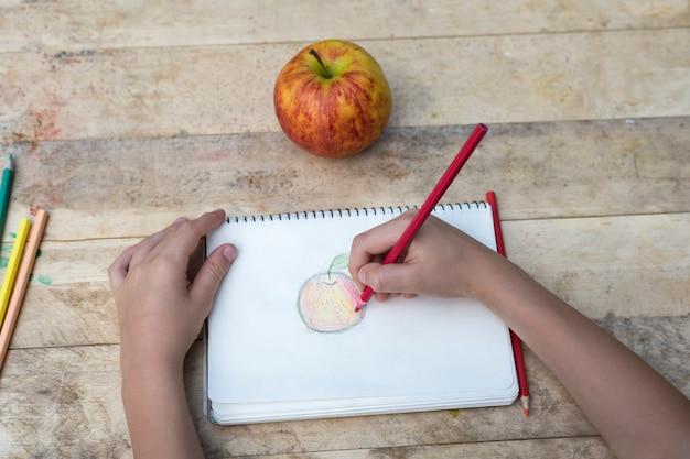 Ręce dzieci rysują jabłko za pomocą kolorowych ołówków. widok z góry