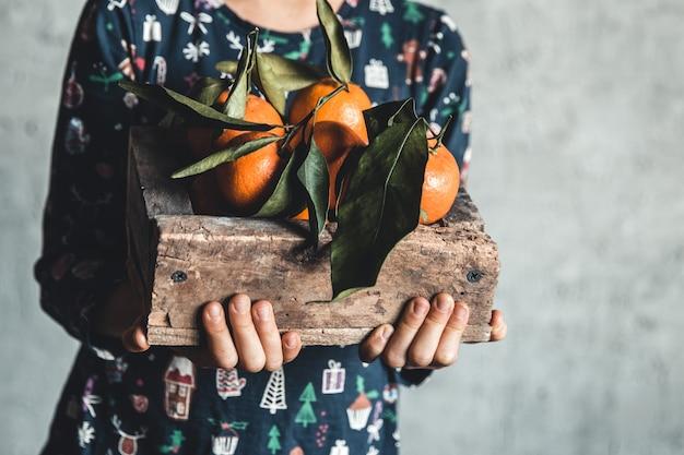 Ręce dzieci trzyma drewniane pudełko z widokiem z góry świeże mandarynki klementynki, miejsce na kopię
