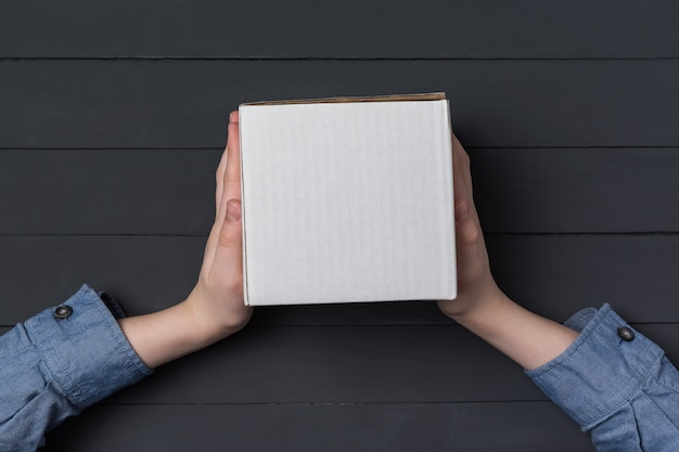 Ręce dzieci trzymają białe kwadratowe pudełko kartonowe. czarne tło.