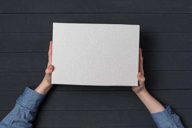Ręce dzieci trzymają białe pudełko kartonowe na czarnej ścianie. widok z góry. koncepcja wysyłki.