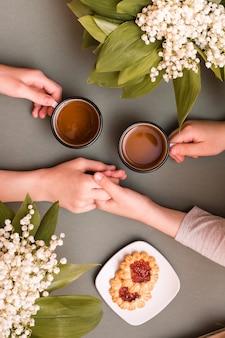 Ręce dzieci trzymają kubki herbaty i siebie nawzajem. spotkanie i picie herbaty. widok z góry i z pionu