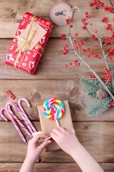 Ręce dzieci trzymają lizak w jasne paski i prezent na drewnianym stole i gałęzi z czerwonymi jagodami
