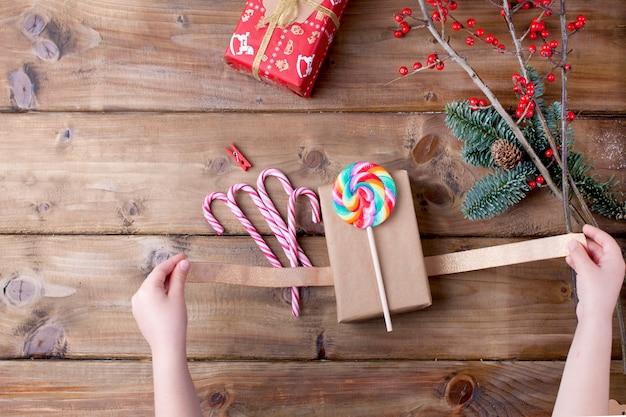 Ręce dzieci trzymają lizak w jasne paski i prezent na drewnianym stole i zielonej gałęzi