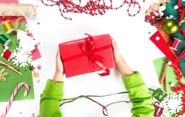 Ręce dzieci trzymają prezent na boże narodzenie. dekoracja przedstawia tworzenie płaskiego widoku z góry boże narodzenie przygotowanie uroczystości diy koncepcja wystroju na białym tle.