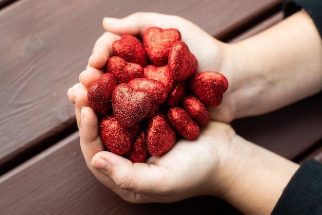 Ręce dzieci trzymają wiele czerwonych błyszczących serc. walentynki. miłość, 14 lutego. pojęcie miłości, zaufania, wiary, pomocy.