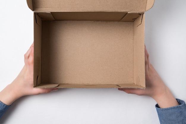 Ręce dzieci trzymających otwarte pudełko kartonowe. puste pudełko, biała ściana.