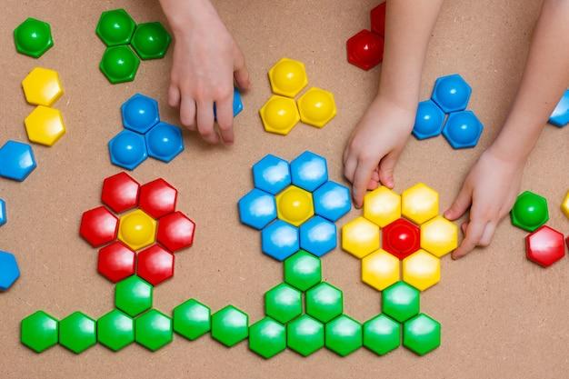 Ręce dzieci wkładają detale kolorowych mozaik w rysunek kwiatów na stole