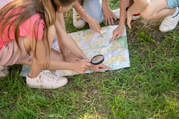 Ręce dzieci wskazujące mapę na trawniku