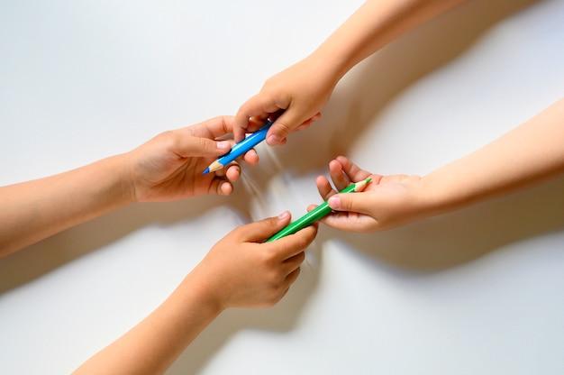 Ręce dzieciaka dzielą się kolorowymi kredkami na białym tle