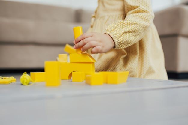 Ręce dziecka bawiące się żółtymi kostkami na szarym drewnianym stole